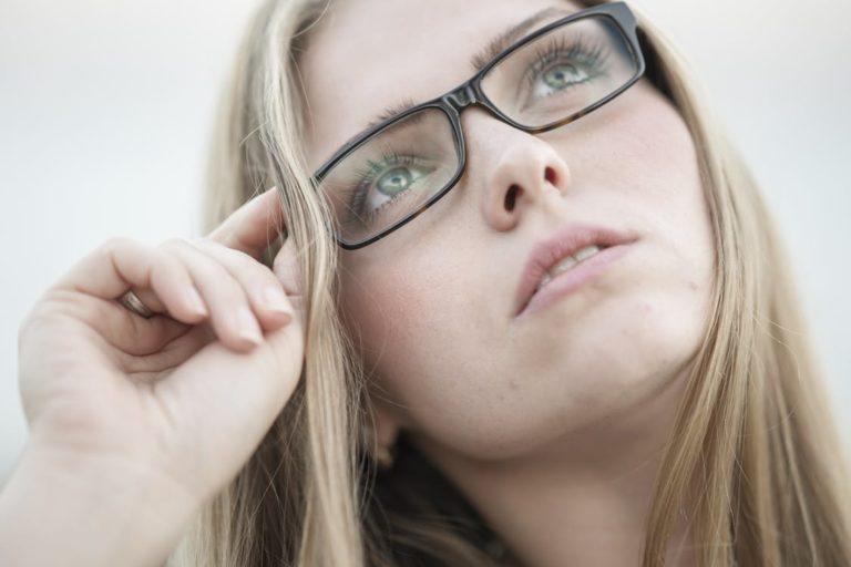 Woman adjusting her glasses.